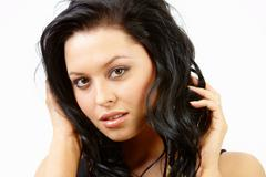 Pretty brunette touching her hair and looking at camera Stock Photos