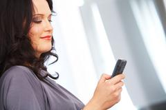 portrait of fashionable businesswoman writing sms on cellphone - stock photo
