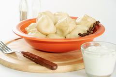 Image of tasty dumplings in plastic bowl served with sour cream Stock Photos