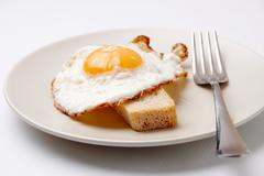 Stock Photo of image of fried egg on plate served with piece of wheat bread