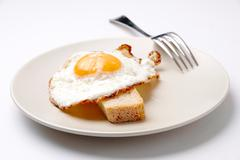 close-up of fried egg on plate served with piece of wheat bread - stock photo