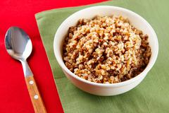 photo of plate of buckwheat with spoon on the table - stock photo