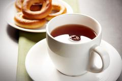close-up of black tea in white cup on the background of desert - stock photo
