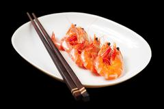 Stock Photo of image of tasty shrimps lying in row with two chopsticks near by