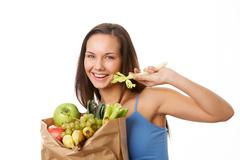 Portrait of pretty girl with paper sackfull of fruits and vegetables while eatin Stock Photos