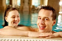 portrait of happy man with pretty girl on background in swimming pool - stock photo