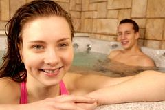 Portrait of happy girl with her boyfriend on background in swimming pool Stock Photos
