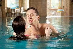 photo of happy man and pretty girl interacting in swimming pool - stock photo