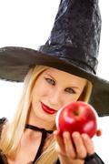 image of witch giving red ripe apple to somebody - stock photo