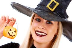 image of witch holding pumpkin candle and looking at camera - stock photo