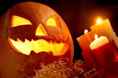 Stock Photo of image of big pumpkin with burning candle inside and three candles near by