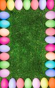 Vertical image composed as colorful egg framing surrounding grassland Stock Photos