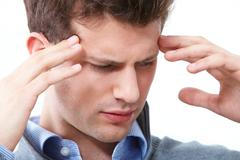 portrait of young man having headache - stock photo