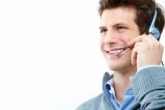 Photo of handsome guy speaking on the headset over white background Stock Photos