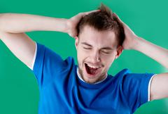 Portrait of young man full of joy over green background Stock Photos