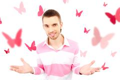 Image of smart guy looking at camera surrounded by pink paper butterflies Stock Photos