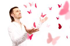 Image of smart guy with open palms looking at pink paper butterflies Stock Photos