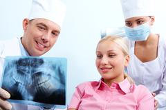 Stock Photo of portrait of woman with dentist showing her x-ray photography behind assistant