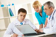 Stock Photo of photo of three colleagues working at new medical project and thinking about it