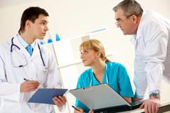 Photo of three clinicians having serious conversation in hospital Stock Photos