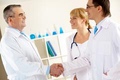 photo of aged physician and young clinician looking at each other while handshak - stock photo