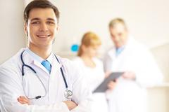 Portrait of cheerful doctor looking at camera and smiling with working clinician Stock Photos