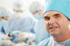 portrait of confident senior surgeon looking at camera on background of working - stock photo