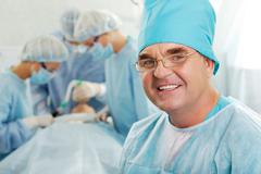 portrait of happy doctor on background of working surgeons - stock photo