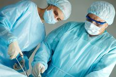a surgeon and a nurse operating - stock photo