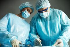 senior doctor operating and a nurse standing with a clamp - stock photo