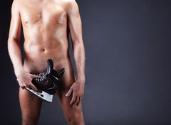 image of naked man with skate isolated over black background - stock photo