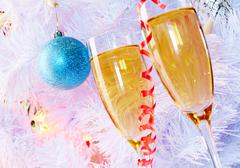 Two champagne flutes with firtree branch behind Stock Photos