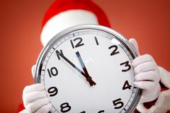 Photo of clock in santa hands showing five minutes to midnight Stock Photos