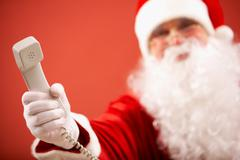 Photo of santa claus giving phone receiver to you Stock Photos