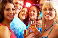portrait of happy young people holding glasses of champagne - stock photo