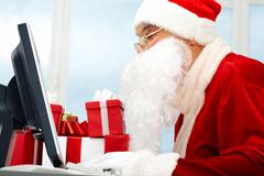 portrait of santa claus in front of computer monitor - stock photo