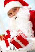 Photo of happy santa claus with red giftbox looking at camera Stock Photos