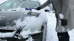 Woman coat clean remove snow car window capote brush tool winter Stock Footage