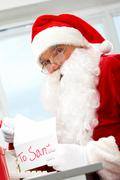photo of happy santa claus opening letter with christmas wish - stock photo