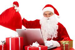 portrait of santa claus in front of laptop with gifts near by - stock photo