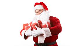 photo of happy santa claus with giftboxes looking at camera - stock photo