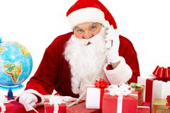 Portrait of santa claus with giftboxes speaking on the phone and looking at came Stock Photos