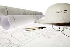 close-up of blueprints with sketches of projects, helmet, eyeglasses and divider - stock photo