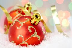 Red christmas baubles with golden decor against glaring background Stock Photos