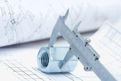 image of architectural ruler over nut with house project near by - stock photo