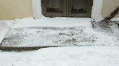 Man sweeper clean  broom snow tiles house door entrance Stock Footage