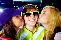 two happy girls kissing smiling guy during party - stock photo