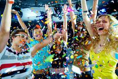 Photo of excited teenagers in confetti raising their arms expressing joy photo o Stock Photos