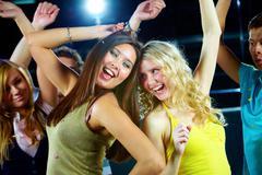 Two glamorous girls enjoying themselves while dancing in night club Stock Photos