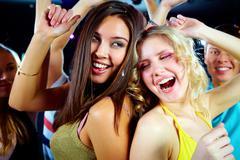 two joyful girls dancing in night club and having fun - stock photo